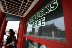 Visitors take a break at Starbucks Coffee at the Forbidden City on Sept. 6, 2005, in Beijing, China.