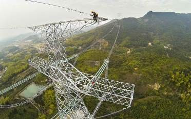 Electricians work on a 1,680-kilometer-long high-voltage DC transmission line in Zhejiang Province.