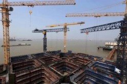 Cranes and workers are seen at a construction site at a main pier of the Hutong Yangtze River highway and railway bridge above the Yangtze River, in Nantong, Jiangsu Province, China, April 25, 2015.