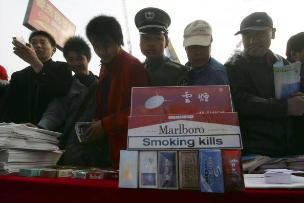 People examine fake cigarettes during a promotional event of World Consumer Rights Day in Beijing, on March 15, 2007.