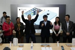 Apple Inc. CEO Tim Cook next to tech representatives from China at an Apple store.