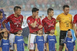 Players of Guangzhou Evergrande use their shirts to protect the ball kids from heavy rain during a match at Tianhe Sports Center in Guangzhou, China, on May 5, 2015.