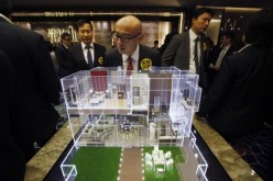 A real estate agent looks at a housing model displayed by a property developer in Hong Kong.
