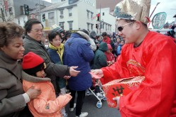 A man in a traditional Treasury God costume hands out red packets, the lucky money, at the annual Chinese New Year Parade in the Chinatown, Washington, D.C., on Feb. 21, 1999.