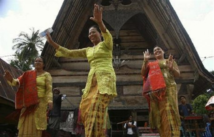 Sumatran women dance the Tor-tor folk dance to welcome tourists at the Tuk-tuk village in Samosir, Indonesia's North Sumatra Province.