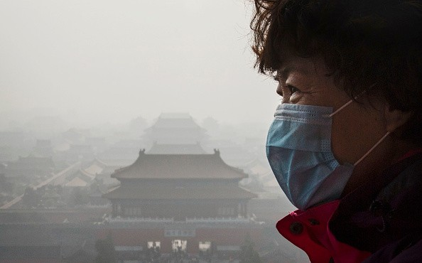 A Chinese woman wears a mask as haze from smog caused by air pollution hangs over the Forbidden City in Beijing, China, on Nov. 15, 2015.