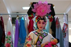 An artist of a Chinese opera troupe poses for a photo in the backstage.
