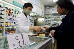 A pharmacy employee attends to a customer in downtown Shanghai, China, on April 25, 2003.