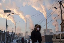 Smoke billows from stacks as a Chinese woman wears as mask while walking in a neighborhood next to a coal fired power plant on Nov. 26, 2015 in Shanxi, China.