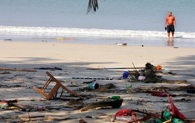 A Swedish tourist wades in the ocean along a garbage strewn and tsunami-struck beach December 27, 2004 in Phuket, Thailand.