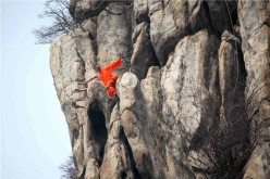Shaolin kung fu masters practice on a cliff at Songshan Mountain in Dengfeng, Central China's Henan Province, March 17, 2016.