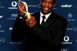 US basketball legend Dikembe Mutombo poses with his award for 'Sport For Good ' in the Awards room.