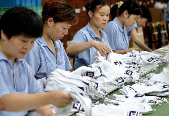 Workers prepare socks at a facility in Shanghai. China's manufacturing sector is being hit hard by the country's aging population.