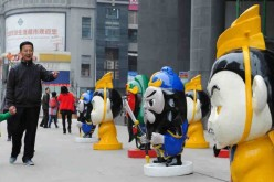 Locals walk by the cartoon figures of the Three Kingdoms period (AD 220-280) in front of a shopping mall in downtown Zunyi, Southwest China's Guizhou province, on April 1, 2016.