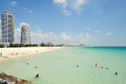 Vacationers enjoy the fine weather and the shallow clear waters of Miami Beach in Florida.