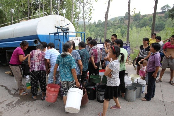 Villagers crowd around to receive water in Luoyang, Henan Province, on Aug. 4, 2014.