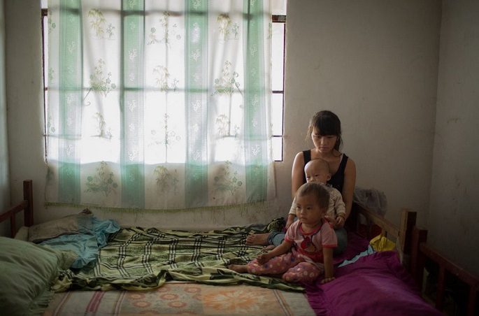 Not siblings: Xiao Mei, 16, holds her 1-year-old son as they and her 2-year-old daughter pose for a picture.
