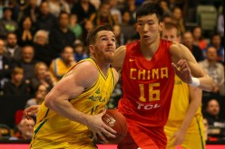 Chinese center Zhou Qi defends against Australia's Lucas Walker.