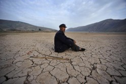 A villager sits alone on a dried-up riverbed in Gulang County on July 15, 2009 in Gansu Province, northwest China.
