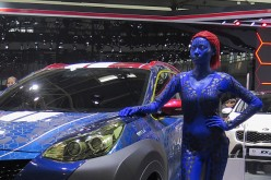 A model stands by a KIA vehicle at the Beijing International Automotive Exhibition on April 25, 2016 in Beijing, China.