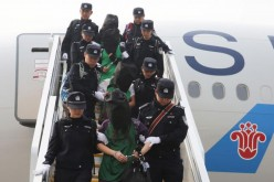 Police escort a group of people wanted for suspected fraud in China after they were deported from Kenya.