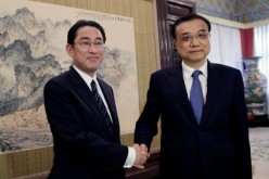 Japanese Foreign Minister Fumio Kishida poses with Chinese Premier Li Keqiang during their meeting in Beijing on Saturday, April 30.