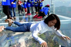 A female tourist lie on the glass sightseeing platform.