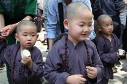 Kids wearing Buddhist clothing take part in an event of