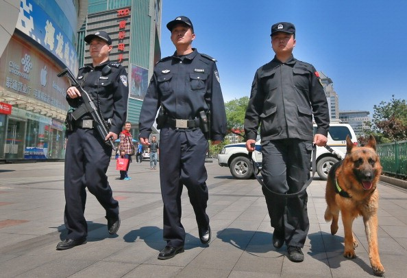 Police officers and a dog patrol a street on May 12, 2014 in Beijing, China.