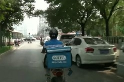 To the rescue: Restaurants in China cater to college students who can't go out of their campus through their food delivery service. (Above) A delivery guy heads to his next customer.